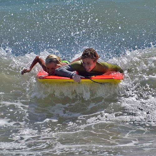 Image of boys riding boogie boards