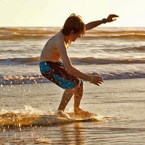 Image of boy skim boarding